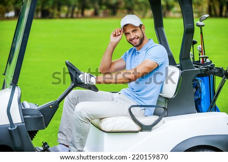 Man driving golf cart. Side view of handsome young man driving a golf cart and looking at camera - stock photo