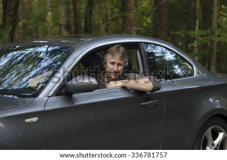 Man driving his car in the country saying hello