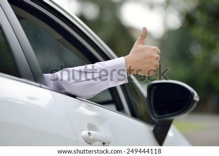 Man driving his car with thumbs up. Automotive concept photo