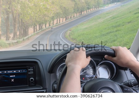 man driving into long road