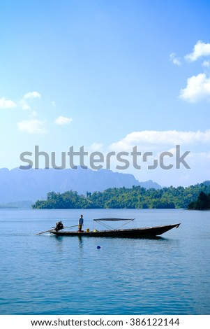 Man driving long tail boat in the sea