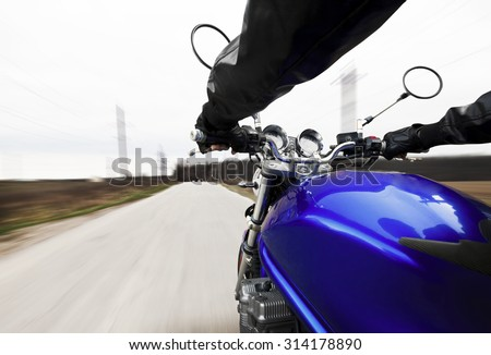Man driving on motorcycle on big speed on asphalt road - stock photo