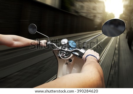 Man driving on scooter at old streets in city - stock photo