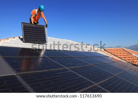 Man during intallation of alternative energy photovoltaic solar panels on roof - stock photo