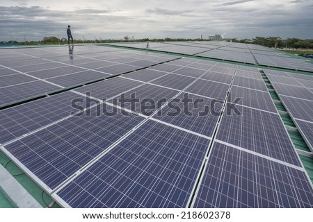 Man during survey of alternative energy photovoltaic solar panels on roof - stock photo