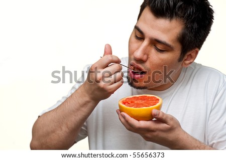 man eating a grapefruit - stock photo