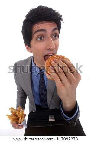 Man eating a hamburger and fries - stock photo