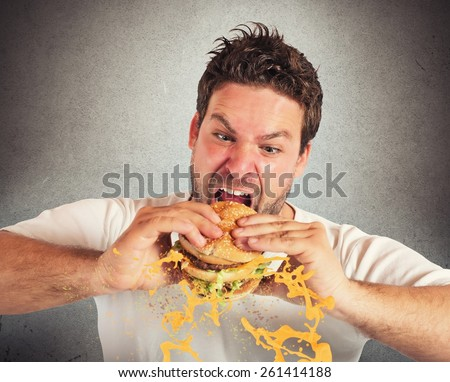 Man eating a sandwich with violent impetuosity - stock photo
