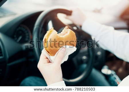 Man eating an hamburger and driving seated in his car