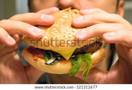 Man eating an hamburger in a fast food