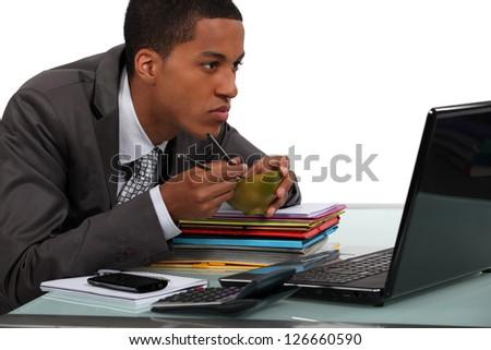 Man eating Chinese food at a laptop - stock photo