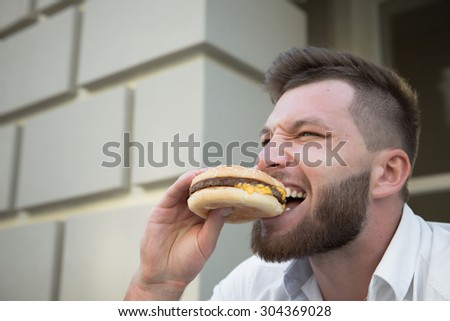 Man eating hot hamburger after stressful work. Close-up of hipster bearded man eating delicious hamburger outdoors.