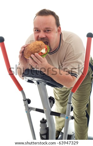 Man eating huge hamburger while resting on a trainer device - isolated - stock photo