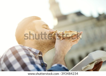 Man eating pizza snack outdoors.Handsome young man eating a slice of pizza outside on the street. - stock photo