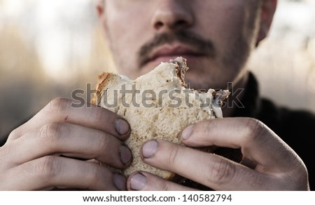 Man eating with dirty hands - stock photo