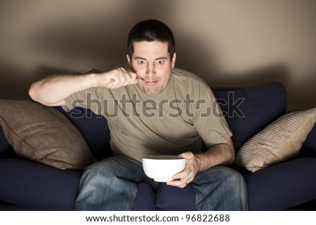 Man eats ice cream while fascinated by the TV - stock photo