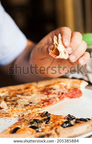 Man eats pizza. Close up pizza piece in hand