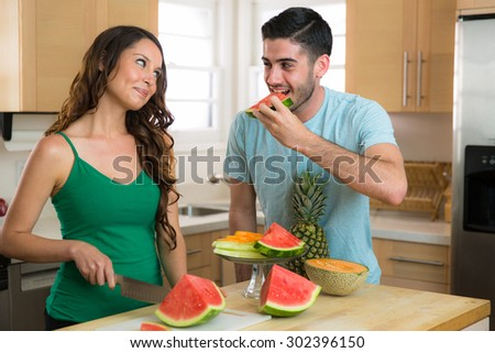 Man eats watermelon handsome boyfriend stealing bite kitchen from wife fruit