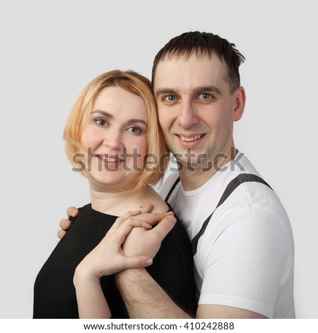 Man embraces woman on gray background in square - Husband and wife portrait - stock photo