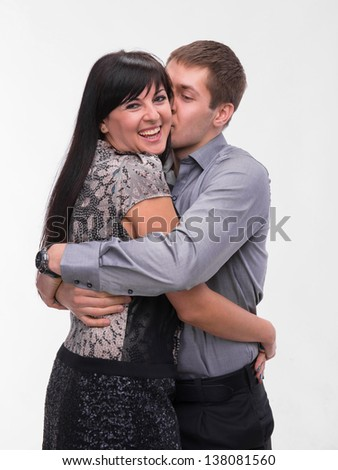 Man embracing and kissing his smiling girlfriend