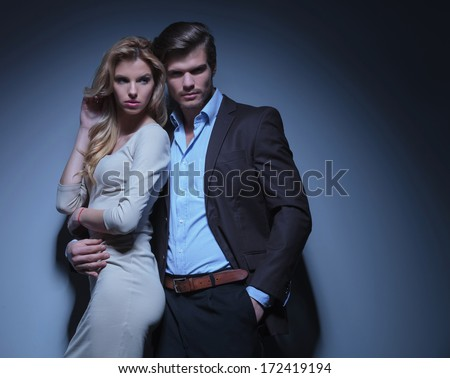 man embracing his woman, she is looking away to her side - stock photo