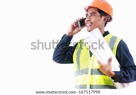 Man engineer holding blueprint, talking on the phone - stock photo