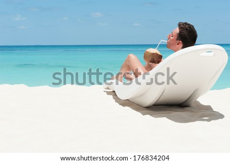 Man enjoy lying on lounger sunbed and drinking coconut cocktail on beach with white sand and blue indian ocean. Summertime at paradise place at Maldives - stock photo