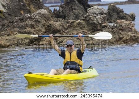 Man enjoying an ocean kayaking trip - stock photo