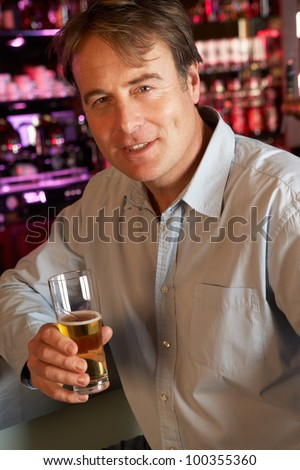 Man Enjoying Drink At Bar - stock photo