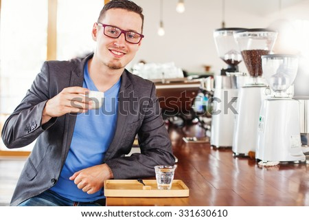 man enjoying his cup of coffee near coffee making machine