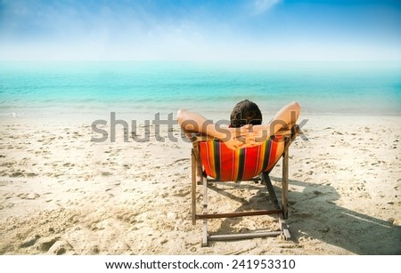 Man enjoying lazy afternoon at the beach. - stock photo