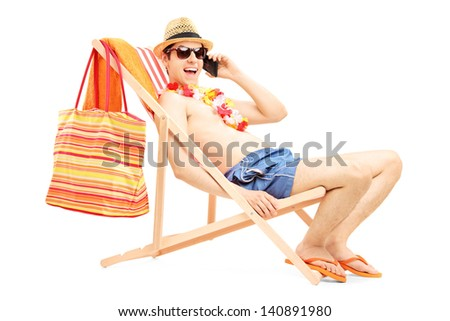 Man enjoying on a sun lounger while talking on a mobile phone, isolated on white background - stock photo
