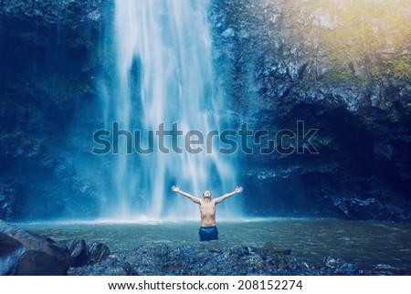 Man enjoying pool at the base of large waterfall in Hawaii - stock photo