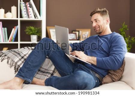 Man enjoying the modern technology at home    - stock photo