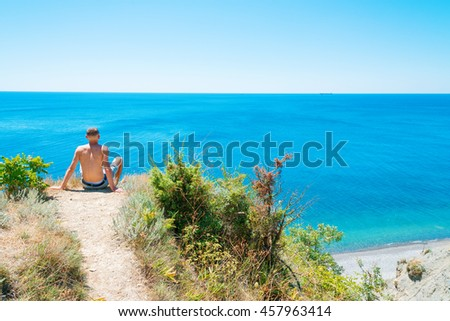Man enjoys views of the sea. A relax on the seashore. Supervision over the horizon. Rest of the athlete at mountain top. - stock photo