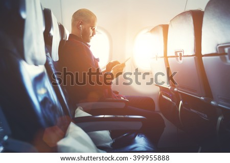 Man entrepreneur is watching video on mobile phone, while is sitting in plane near window with sun rays during his business trip. Hipster guy is listening to music in headphones via cell telephone - stock photo