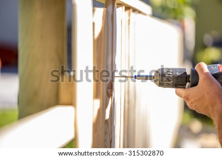Man erecting a wooden fence outdoors using a handheld electric drill to drill a hole to attach an upright plank, close up of his hand and the tool in a DIY concept. - stock photo