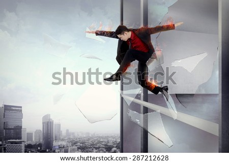 Man escape from office through window with flame all over body. Risky business conceptual - stock photo