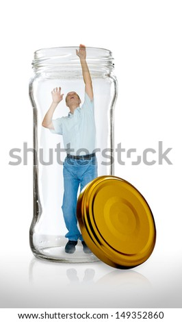 Man escaping from a  glass jar with the open gold color lid - stock photo