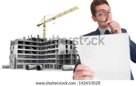 Man examining a document through a magnifying glass, in a construction site