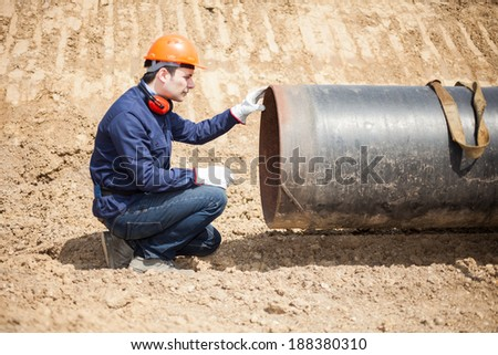 Man examining a pipe in a construction site - stock photo