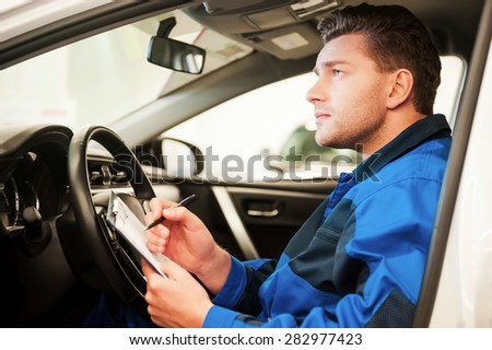 Man examining car. Confident young man examining car and writing something in clipboard while sitting in a car at workshop