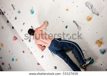 Man exercising at a climbing wall in a gym - stock photo