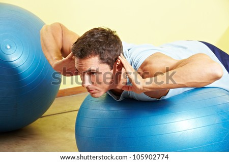Man exercising his back on gym ball in fitness center - stock photo