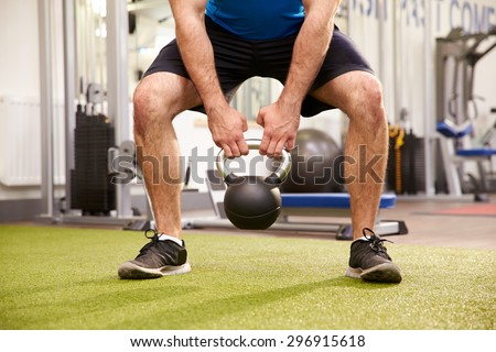 Man exercising in a gym with a kettlebell weight, crop - stock photo