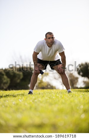 Man exercising outdoor while listening music at his smart phone - stock photo