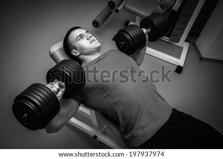 Man exercising with dumbbells.Black and white - stock photo