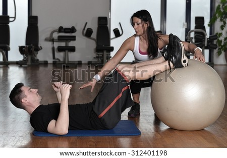 Man exercising with his personal trainer at the gym.