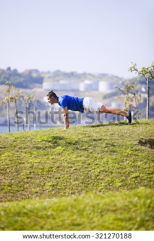 Man exercising with push ups in a Lisbon public park - stock photo