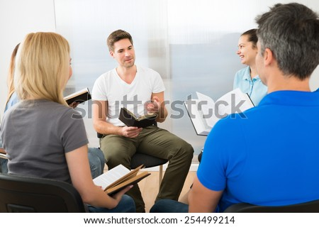 Man Explaining To His Friends From Scripture - stock photo